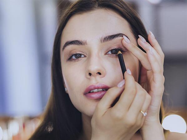 Mujer pintándose la raya del ojo